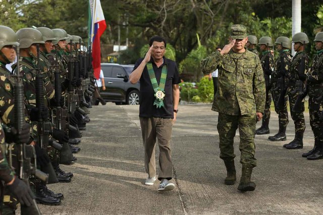 'I TRIED.' President Rodrigo Duterte is accompanied by 6th Infantry Division Commander Brigadier General Arnel dela Vega as he walks past honor guards upon his arrival at the 6th Infantry Division headquarters in Camp Siongco, Awang, Maguindanao on January 27, 2017. Malacañang photo