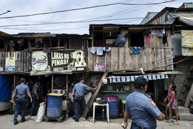 DRUG WAR. Police conduct 'Oplan Tokhang' – a house-to-house campaign to make drug suspects 'surrender' – at an informal settlers community in Manila on October 6, 2016. File photo by Noel Celis/AFP